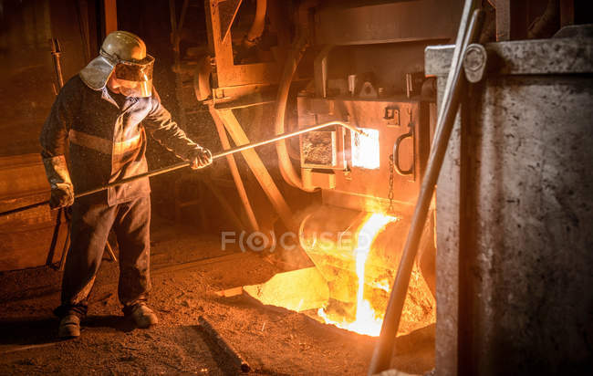 Worker in protective clothing taking sample from furnace in steel foundry — Stock Photo