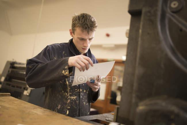 Jovem macho impressora inspecionando o papel para máquinas de impressão na oficina de prensa — Fotografia de Stock