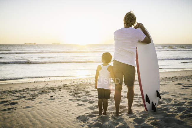 Padre e hijo en la playa, con tabla de surf, mirando al mar, vista trasera - foto de stock