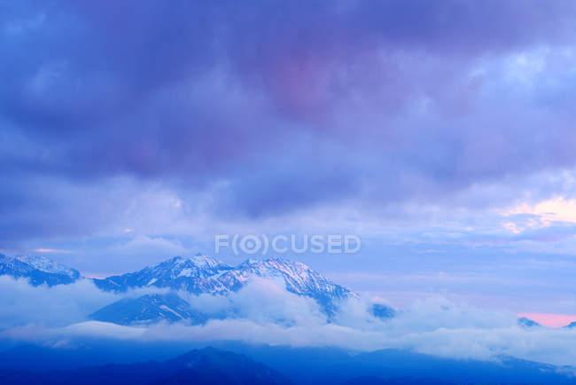 Niebla y nieve capsulado montañas al amanecer, Bolshoy Thach parque, montañas del Cáucaso, República de Adiguesia, Rusia - foto de stock