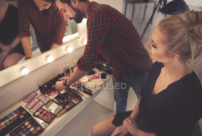 Male make up artist selecting make up for photo shoot — Stock Photo