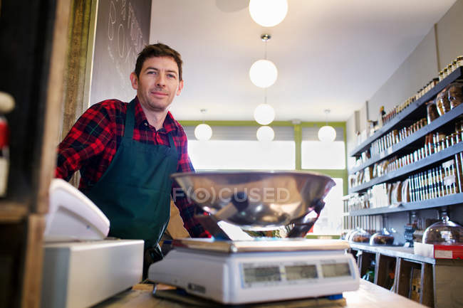 Grocer working behind counter at store — Stock Photo
