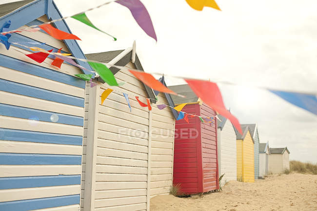 Colorful beach huts and bunting — Stock Photo