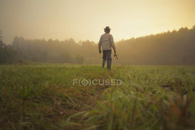 Средний взрослый человек, ходить через поля с удочкой, Sarsy деревне, Свердловская область, Россия — стоковое фото