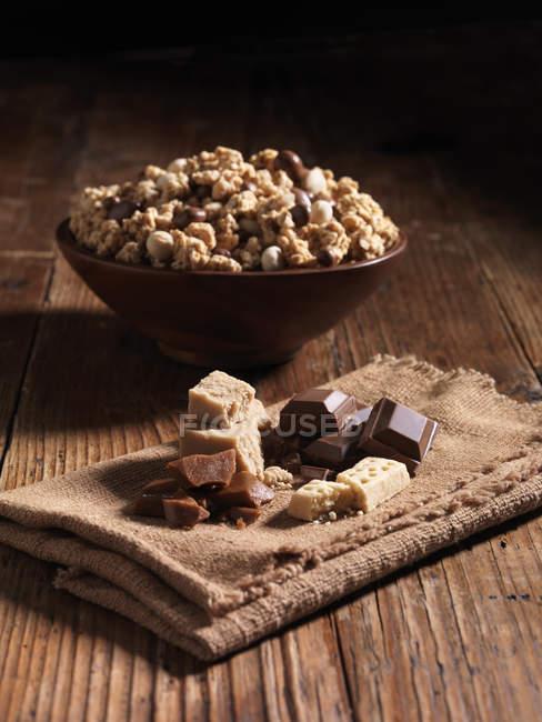 Trituração de milionários caramelo na tigela com ingredientes ao lado — Fotografia de Stock