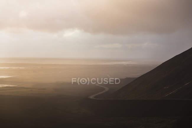 Vue éloignée de la route qui serpente dans le paysage de montagne brumeux — Photo de stock
