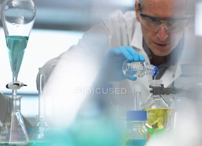Biotechnology, scientist preparing a chemical formula during an experiment in the laboratory - foto de stock