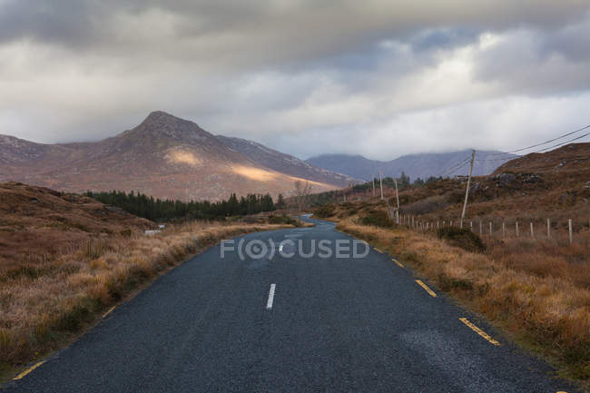 Winding road in mountain landscape under cloudy sky — Stock Photo