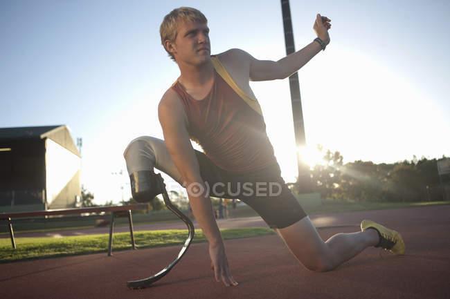 Männlichen Sprinter Dehnung im freien — Stockfoto