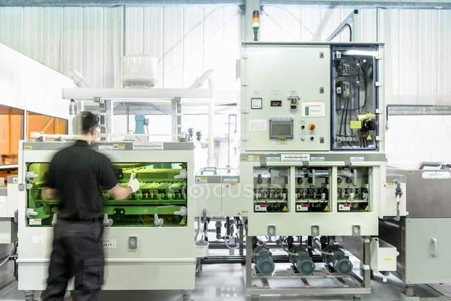 Ouvrier avec la machine de traitement de circuit dans l'usine d'électronique — Photo de stock