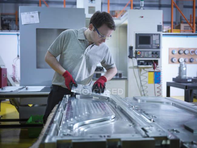 Travailleur inspectant une partie du moule dans une usine de plastique — Photo de stock