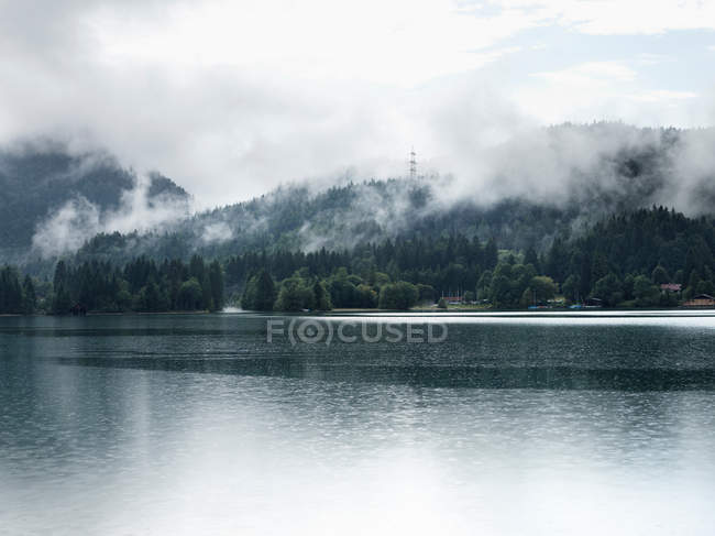 Fog over mountains and still lake — Stock Photo