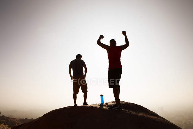 Two male friends, on top of mountain, in celebratory pose — Stock Photo