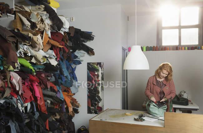 Mujer en el banco de trabajo en el taller de montaje de cuero holdall - foto de stock