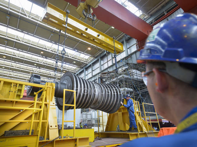 Banksman and crane operator lowering crane to turbine hall during power station outage — Stock Photo