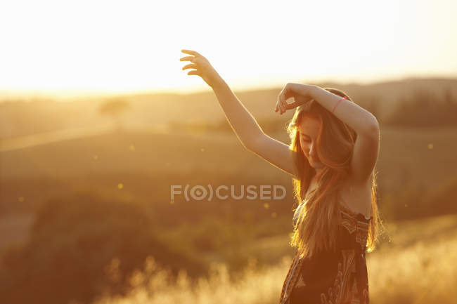Teenager dancing in field at dusk — Stock Photo