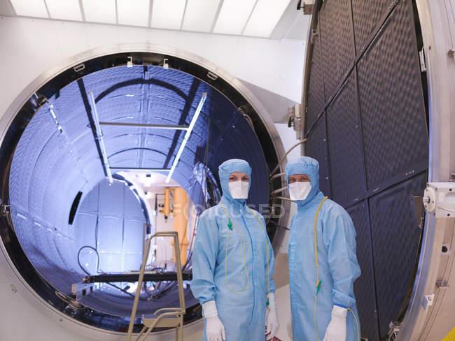 Travailleurs avec la chambre d'essai de satellite — Photo de stock