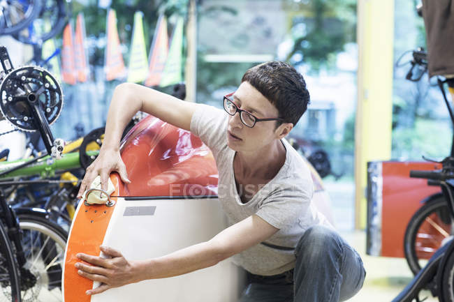 Woman in workshop checking recumbent bicycle bodywork — Stock Photo
