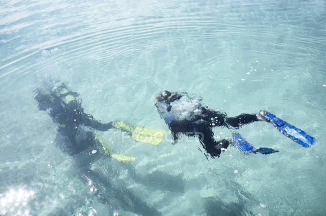 Подводный вид учителя-мужчины и мальчика, ныряющих с аквалангом в море — стоковое фото