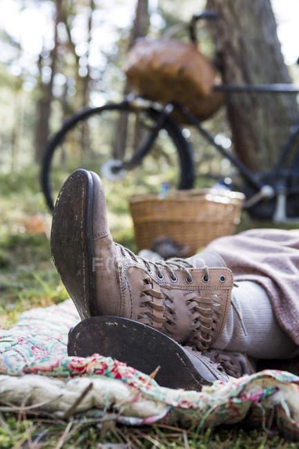 Füße und Knöchel Stiefel von weiblichen Forager ruht auf Decke im Wald — Stockfoto