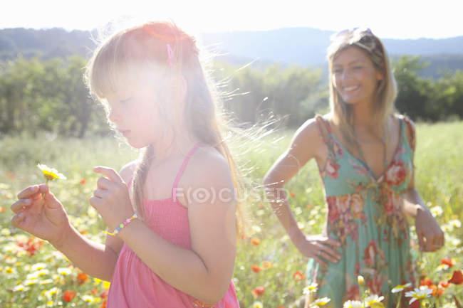 Взрослая женщина и дочь собирают полевые цветы на лугу, Майорка, Испания — стоковое фото