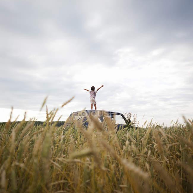 Заднього вигляду молодий хлопчик з піднятими руками стоячи на автомобіль у сфері — стокове фото