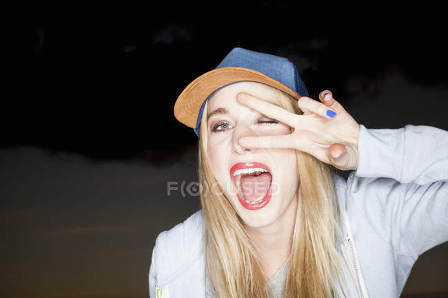 Young woman wearing baseball cap doing peace sign looking at camera open mouthed smiling — Stock Photo