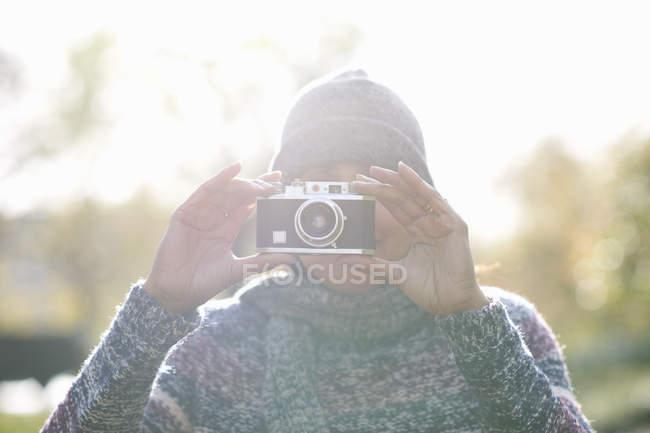 Портрет зрелой женщины, фотографирующей с SLR-камерой в солнечном парке — стоковое фото