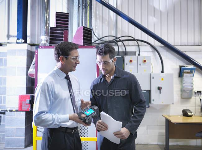 Менеджер офиса и работник обсуждают использование энергии с инфракрасной камерой рядом с котлом на заводе — стоковое фото