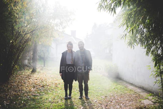Повна довжина фронтальний вид пара стоячи в туманний саду переглядає камери посміхаючись — стокове фото