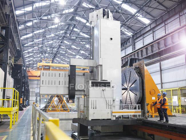 Métallos avec la machine de fraisage de portique dans l'usine d'ingénierie — Photo de stock