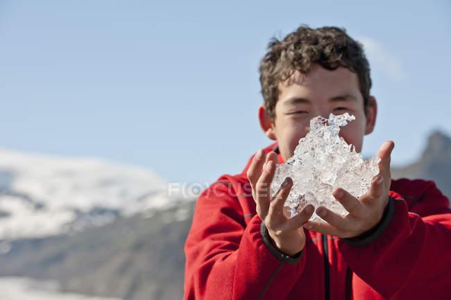 Підлітковий хлопчика, що тримається плавлення iceblock, Fjallsarlon, Скафтафетль, Ісландія — стокове фото