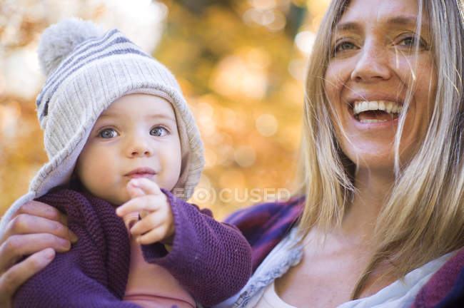 Усміхнена мати тримає дівчинку — стокове фото