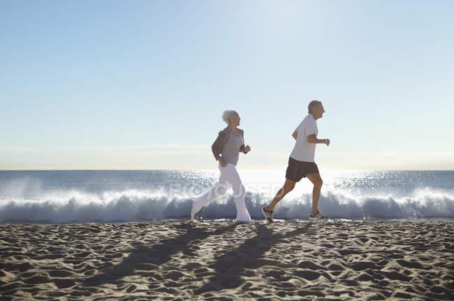 Par de jogging en la playa - foto de stock