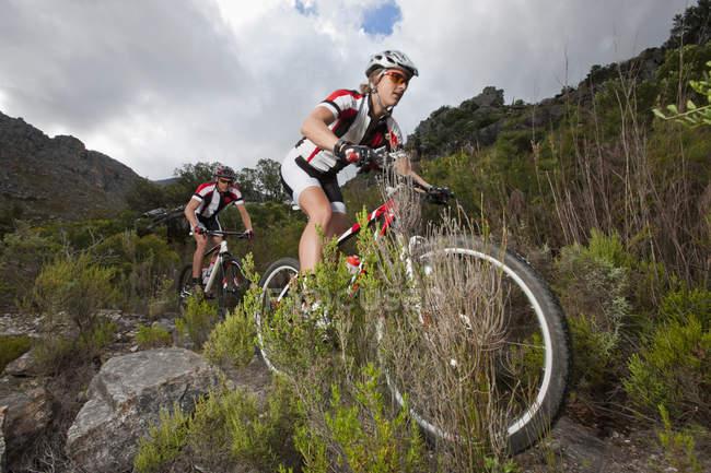 Молодая пара катается на горных велосипедах вниз горы — стоковое фото