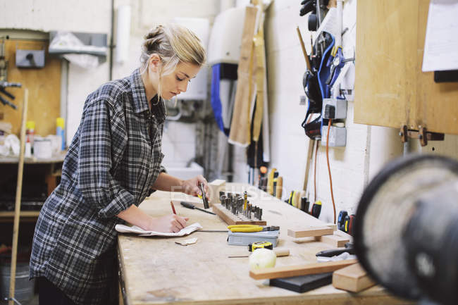 Young craftswoman making notes at workbench in pipe organ workshop — Stock Photo