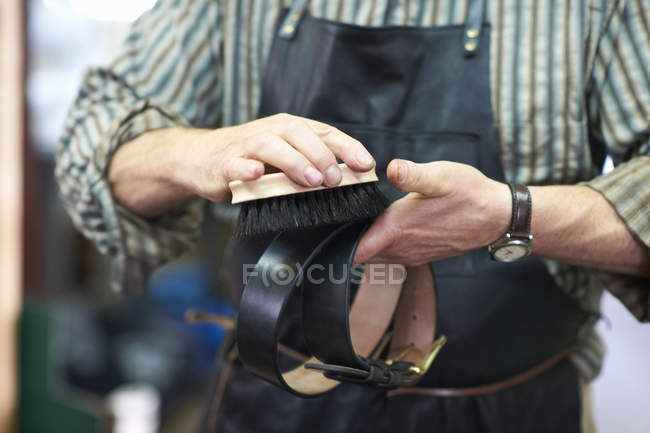 Male worker in leather workshop, polishing belt, mid section — Stock Photo