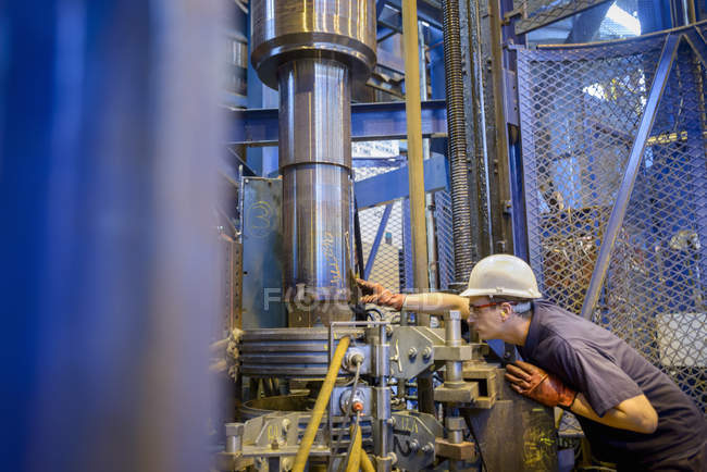 Engineer heat treating steel parts in induction furnace in engineering factory — Stockfoto