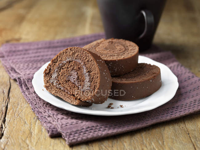 Plate of chocolate sponge rolls on purple cloth napkin — Stock Photo
