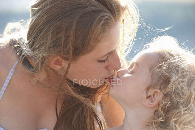 Portrait of young girl kissing older sister — Stock Photo