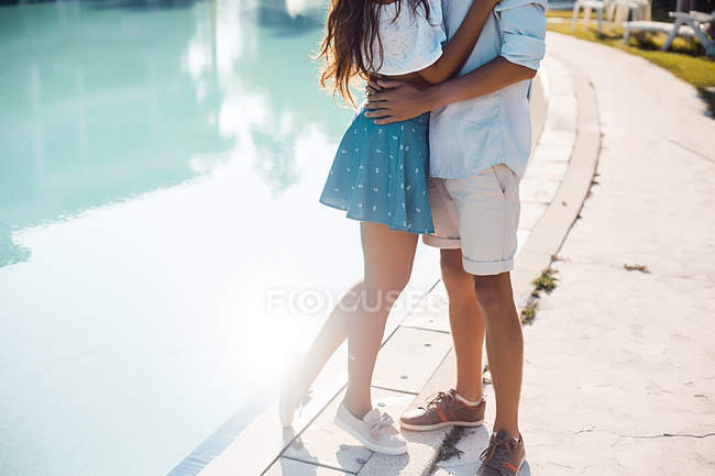 Neck down view of young couple hugging on poolside, Koh Samui, Thailand — Stock Photo