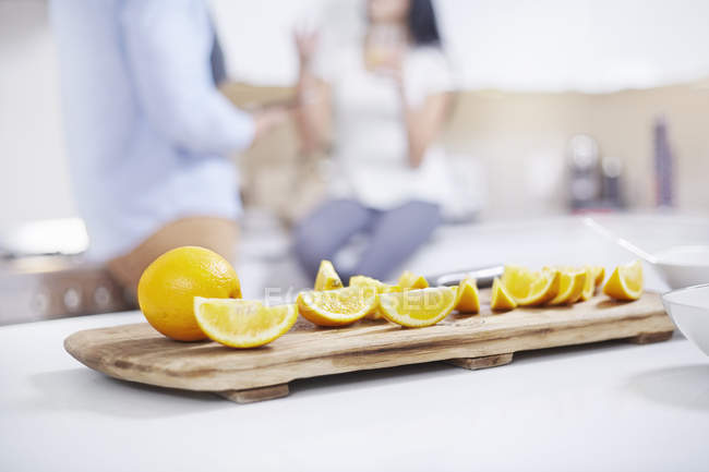 Quartered oranges on kitchen counter with couple on blurred background — Stock Photo