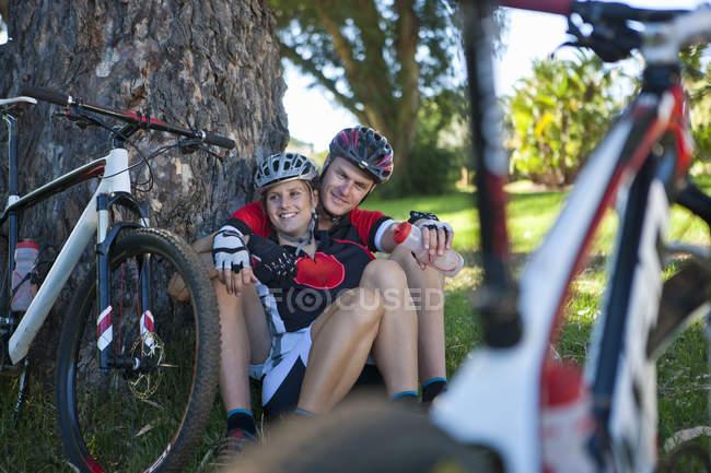 Cyclistes se reposant près d'un arbre — Photo de stock