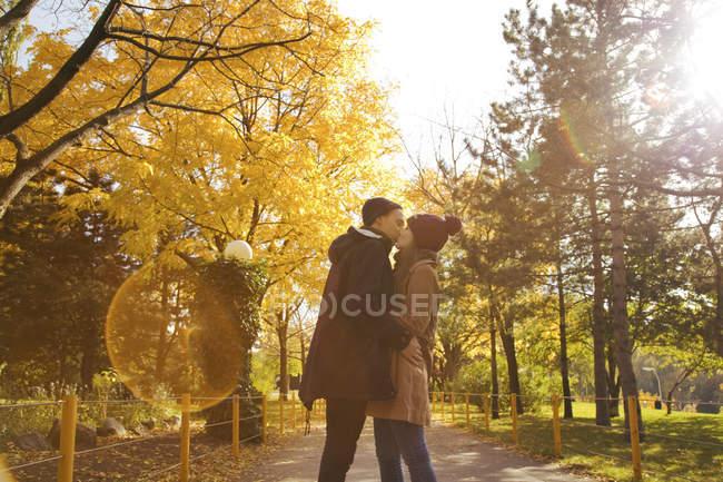 Jovem casal beijando no parque de outono — Fotografia de Stock