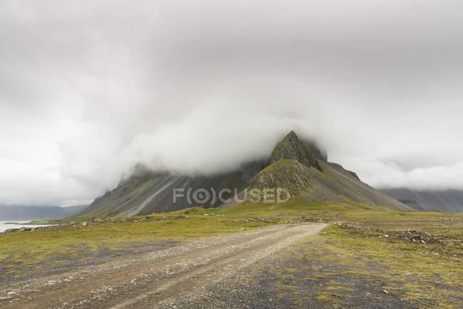 Pista de tierra y nube baja sobre las montañas, Hvalnes, Islandia - foto de stock