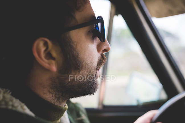 f07b5d66a08e Close up of mid adult man driving and wearing sunglasses — side view ...