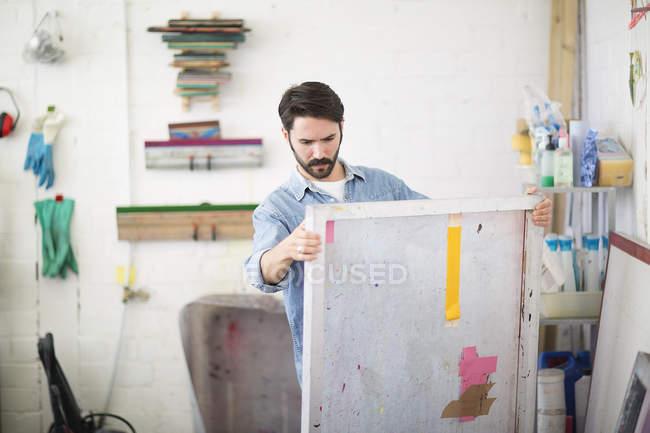 Junge männliche Drucker betrachten Leinwand in Druckereistudio — Stockfoto