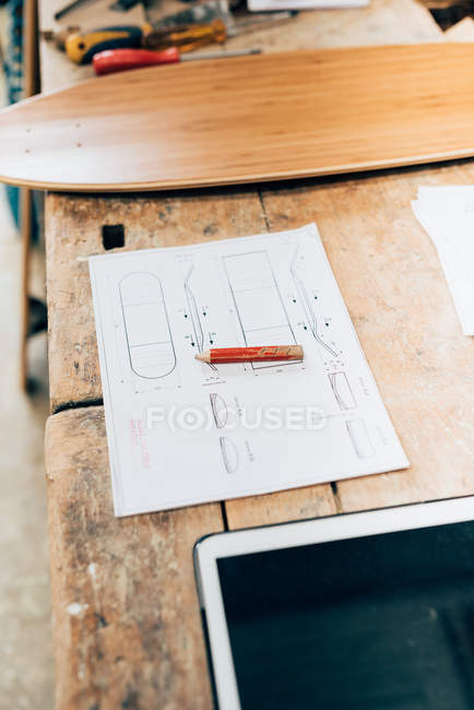 Skateboard, design project and tablet on wooden table in workshop — Stock Photo