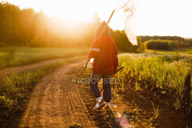 Вид сзади мальчика с бабочка чистой прогуливаясь по грунтовой дороге на закате, Sarsy деревне, Свердловская область, Россия — стоковое фото