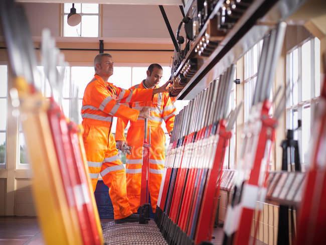 Railway signalmen in signal box pulling lever — Stock Photo